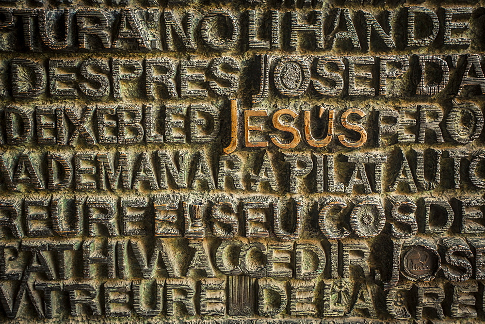 Religious typography on a metal door in Barcelona, Spain.