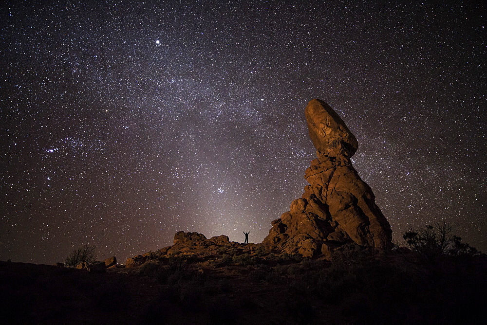 A person provides scale with the Milky Way arcing over Balanced Rock and a rare appearance of Zodiacal Light in Arches National Park.