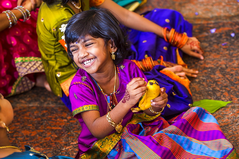 A young girl smiling and laughing at a Hindu wedding in Kuala Lumpur, Malaysia.