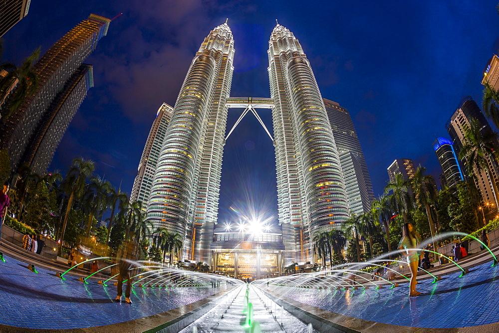 A fisheye nighttime long exposure shot of the Petronas Towers in Kuala Lumpur, Malaysia.