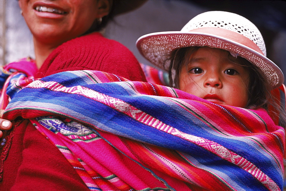A young girl, clad in her best Sunday clothes, is carried to small market in Pisac outside of Cusco, Peru. - 857-8959