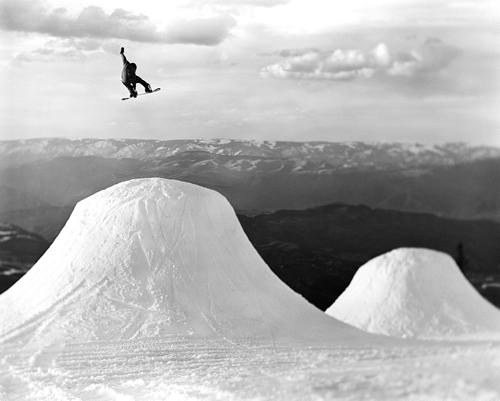 "A snowboarder  jumps a feature in Aspen while filming for ""The Art Of Flight""."