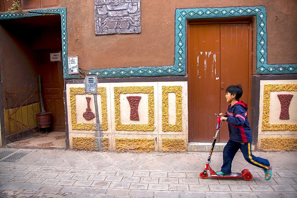 A boy rides on a scooter in Pisac, Peru.