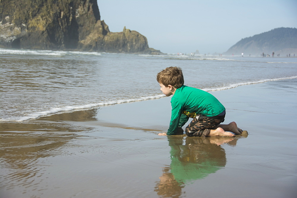Toddler boy digs in the sand and anticipates the waves on Cannon Beach, Oregon.