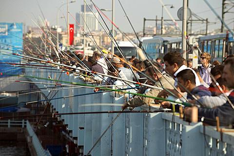 Fishermen and fishing poles line a bridge in Istanbul, Turkey.