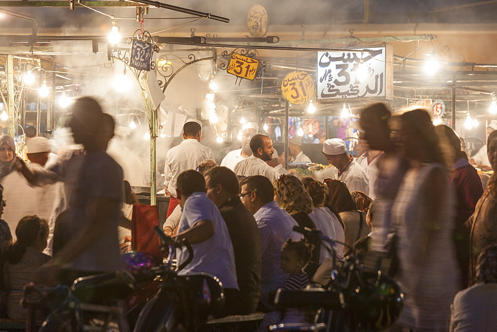Crowds of people sitting and standing at the food stalls in Jemaa EL Fna square in Marrakesh, Morocco.