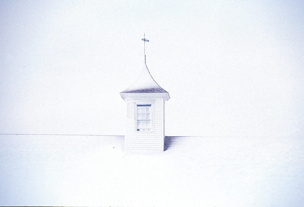 A barn cupola on a post and beam barn in Pownal, ME during a winter storm, United States of America
