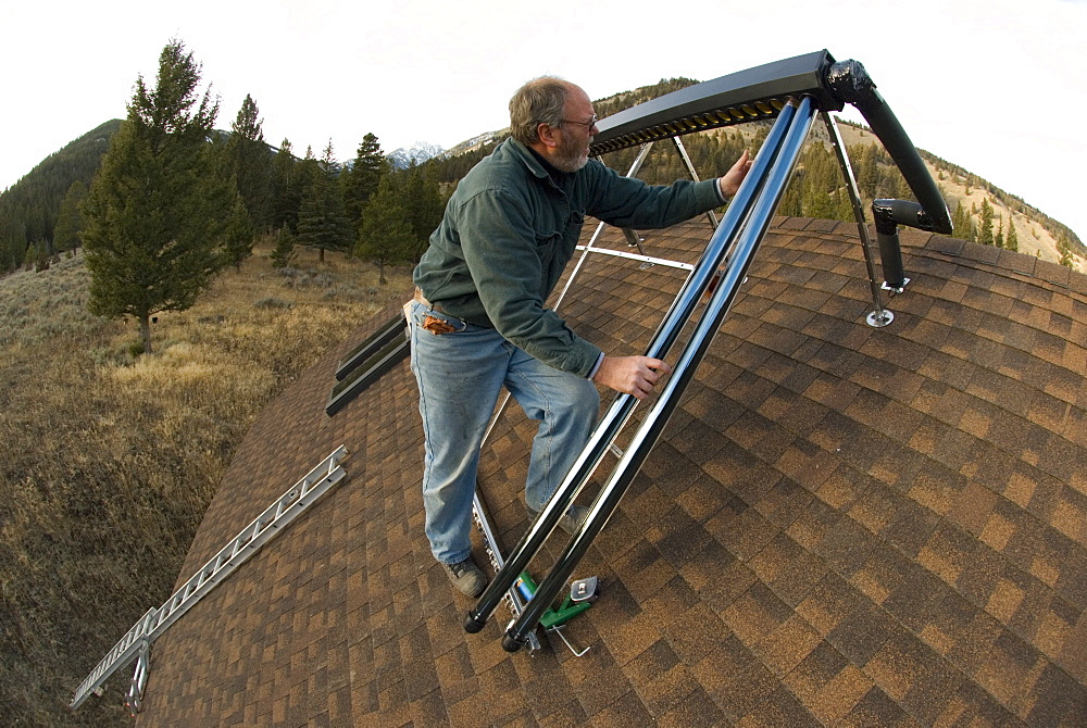Mike McPherson installs an evacuated tube solar hot water system on a roof of a house near Big Sky, Montana, United States of America
