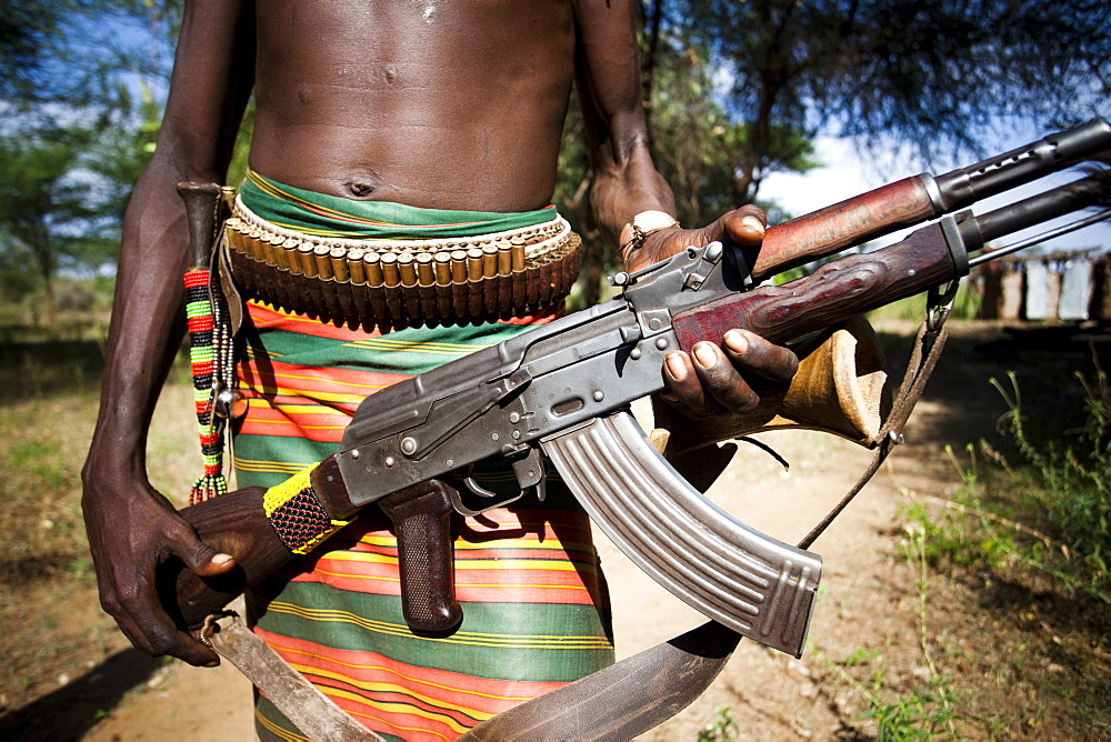 HAMER VILLAGE, OMO VALLEY, ETHIOPIA. An Ethiopian man holds a kalashnikov rifle at his waist, Ethiopia