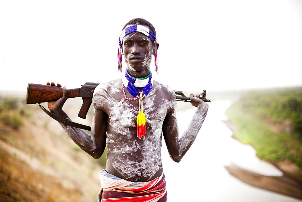KARO VILLAGE, OMO VALLEY, ETHIOPIA. A young man holds his kalashnikov rifle while overlooking the Omo river in the remote Omo Valley of Ethiopia. (released: MHP_095_MR_RedKere), Ethiopia