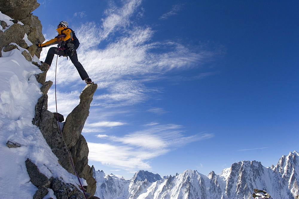 A mountain climber steps across peaks during his ascent of Alpinisme - Aiguille d'Argentiere, France