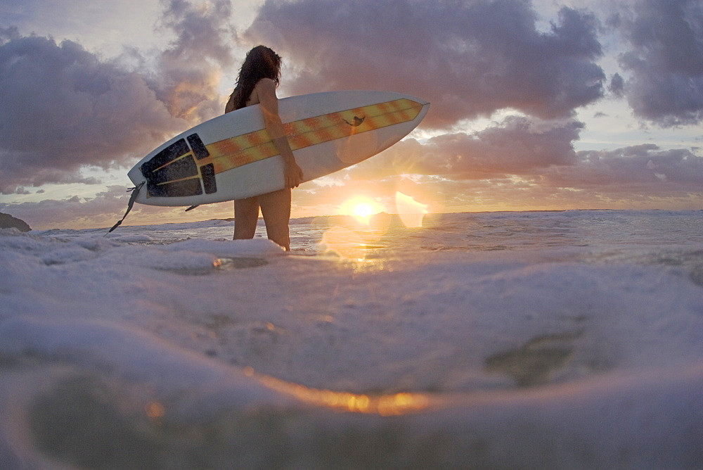 A young woman enters the surf at sunrise. Blueys Beach, Australia, Australia