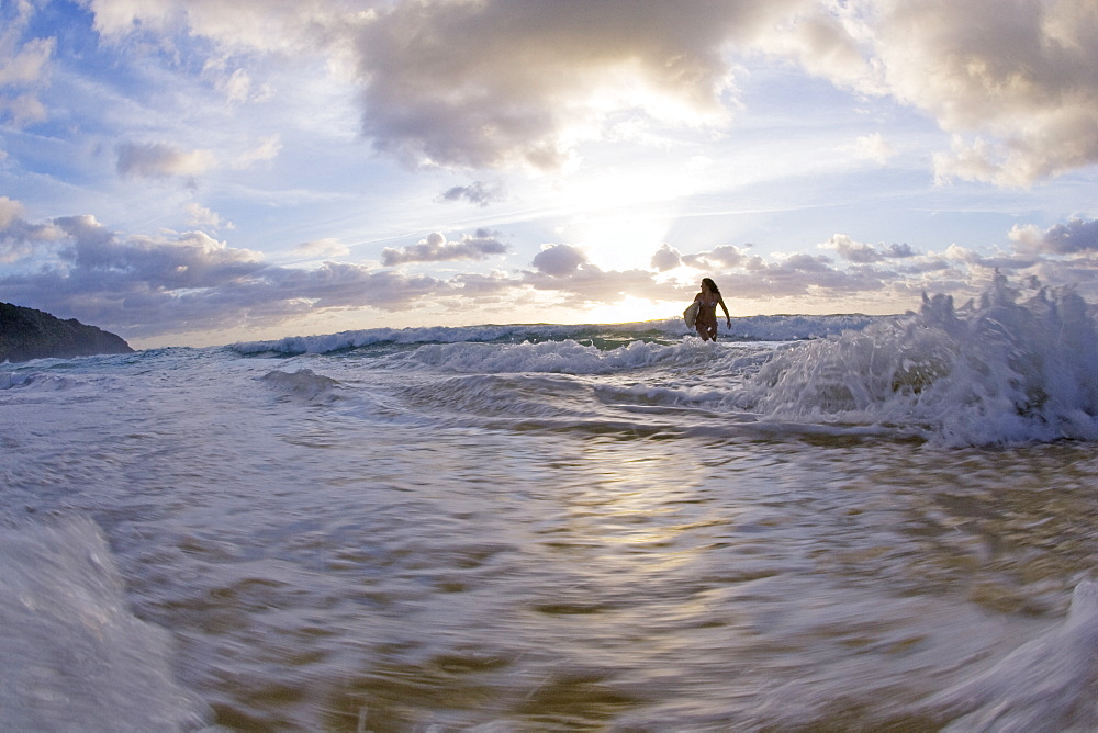A young woman stand in the surf at sunrise. Blueys Beach, Australia, Australia