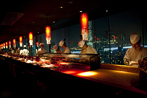 Sushi chefs at Aqua, one of Hong Kong's premiere bars and restaurants, prepare sushi for guests sitting in the main dining room.