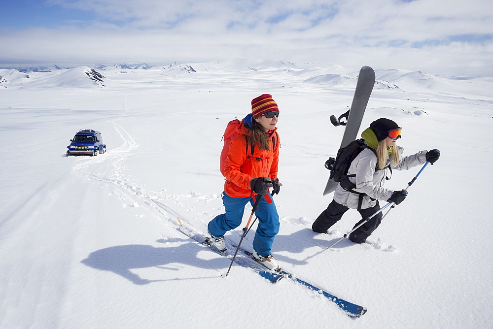 Two girls ski and snowboard touring up Mount Hekla, Iceland