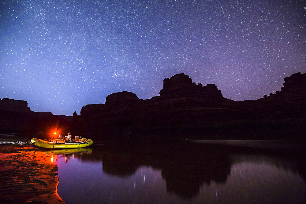 Glowing rafts on waters edge under a night sky.