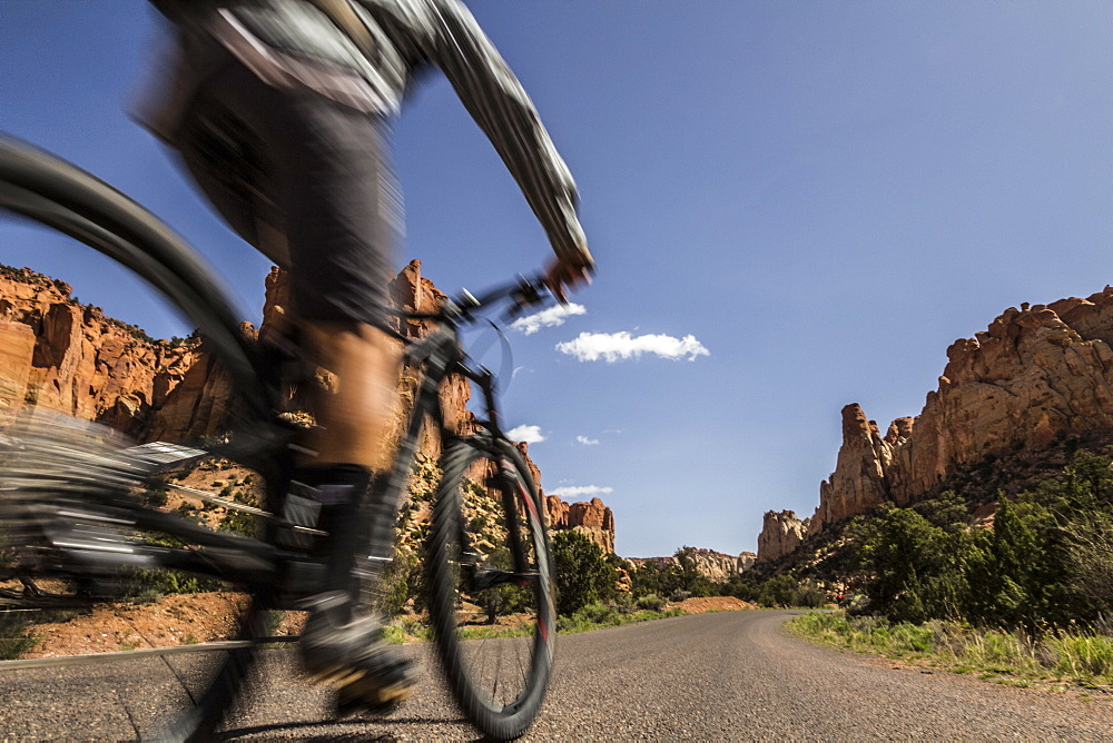 A mountain biker passes by in a blur on a road in southwest desert scenery.