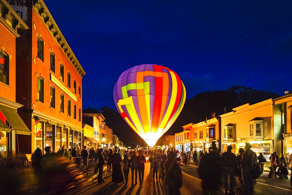 Hot air balloon at dusk with a crowd and building surrounding.