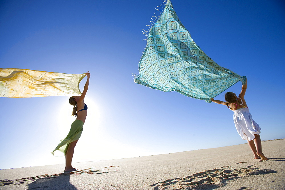 Mother and daughter playing in the wind with colored fabric