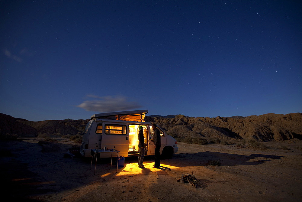 A man and woman stand by their camper van in the desert at night.