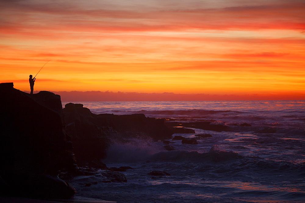 A lone fisherman at sunset.