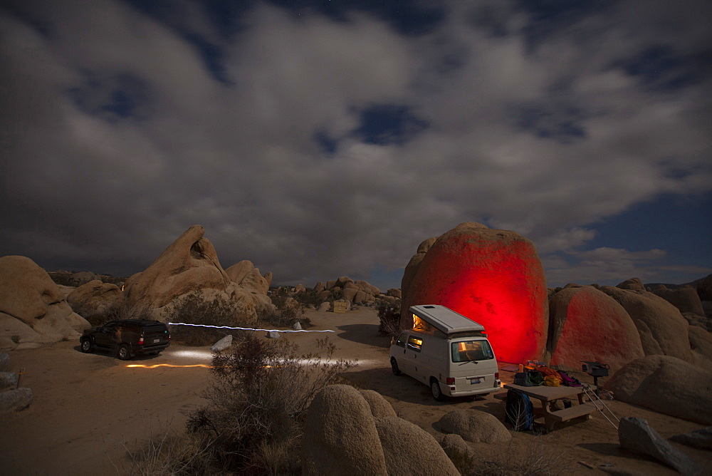 A camper van parked near a glowing red boulder in the desert at night.