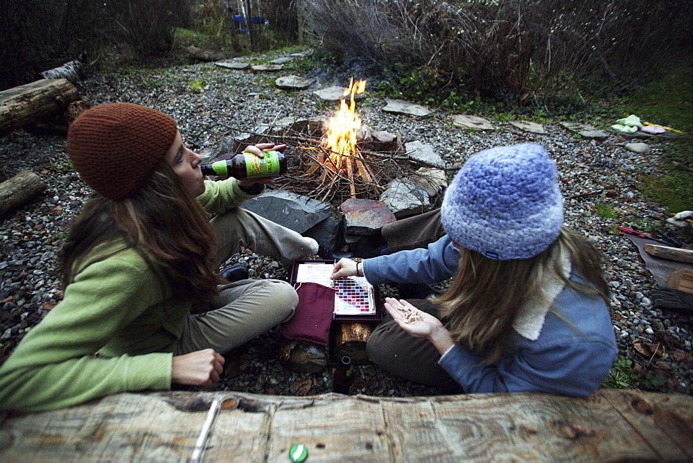 Two women drinking beer playing Scrabble next to a campfire