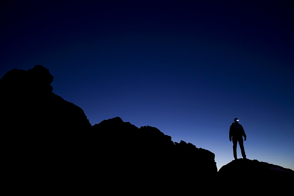 Silhouetted hiker with headlamp at twilight