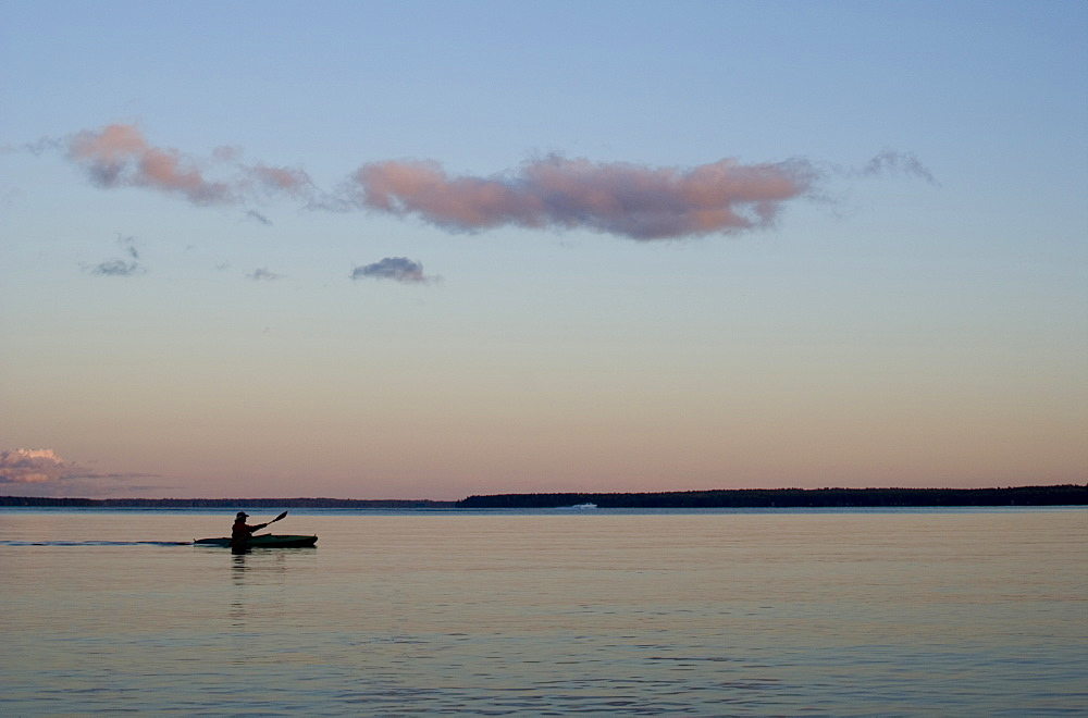 Sea kayaker paddling across still lake at dusk