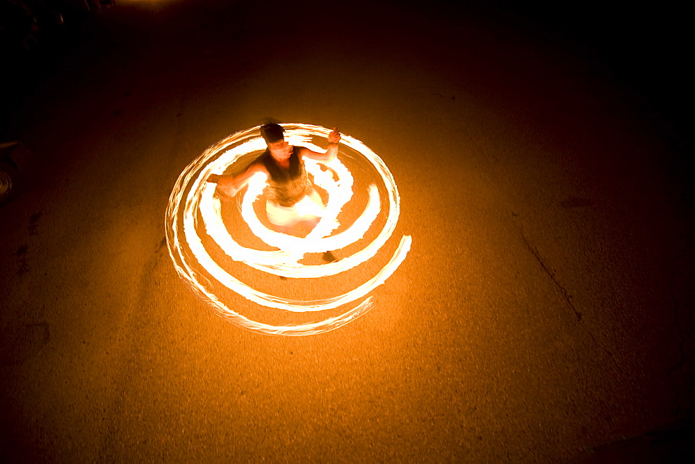 A woman spins fire in a circle wearing a hula hoop in Sandpoint, Idaho.