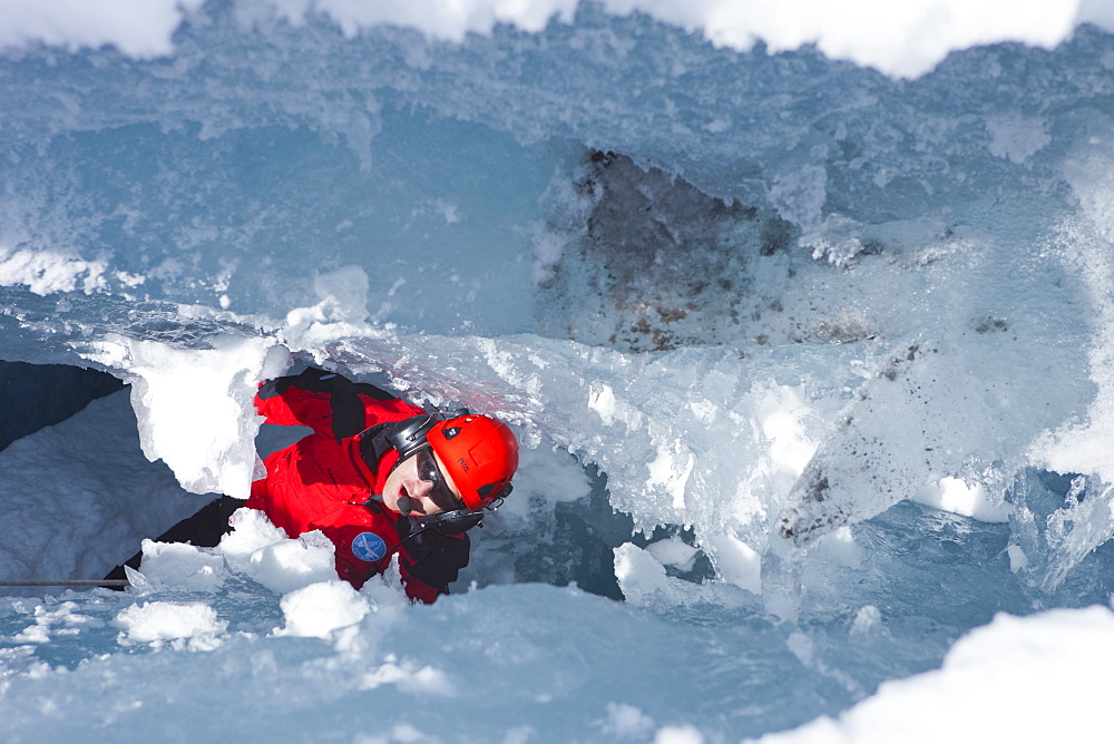 A mountain rescue paramedic is far down in a glacier crevasse, looking up to the surface. In winter the mountain rescue service comes to aid when skiers or climbers tumble down in a hidden crevasse.