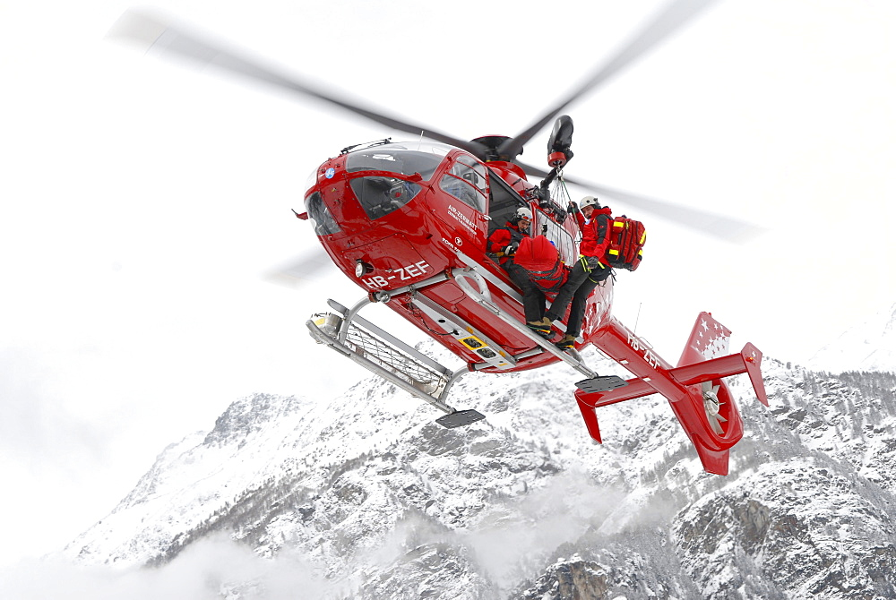 An emergency doctor, patient and paramedic are hanging outside a helicopter during a rescue mission for an injured ski mountaineer.