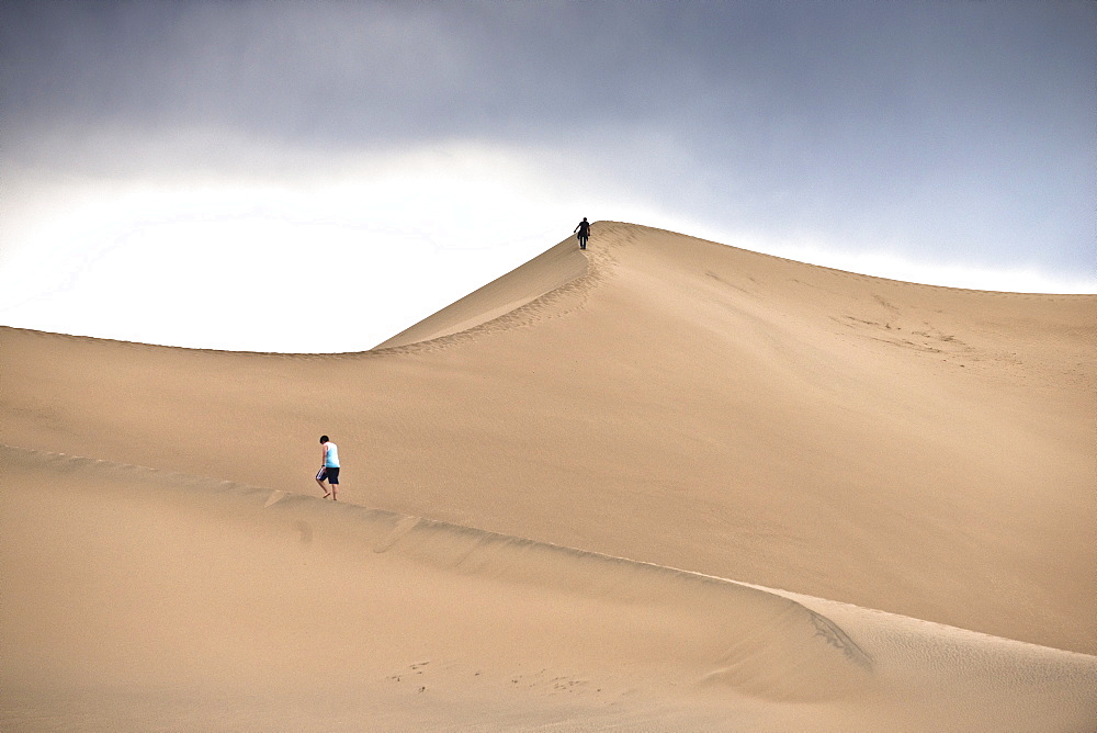 A person hikes up the sand dunes in Death Valley.