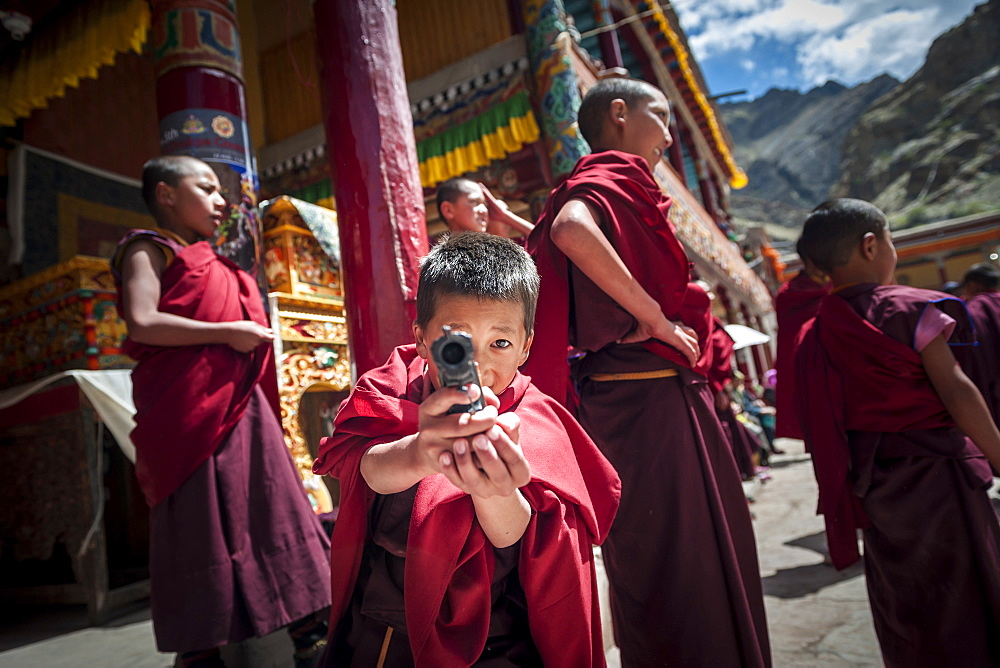 Young monks playing with plastic guns during Hemis Festival, Ladakh, India.