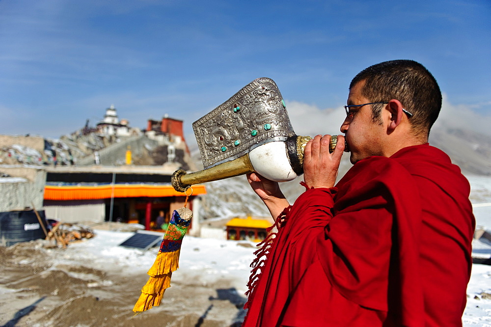A monk playing Tibetan conch shell horn (dungdkar) on a roof of Spitok Monastery, Ladakh, India.