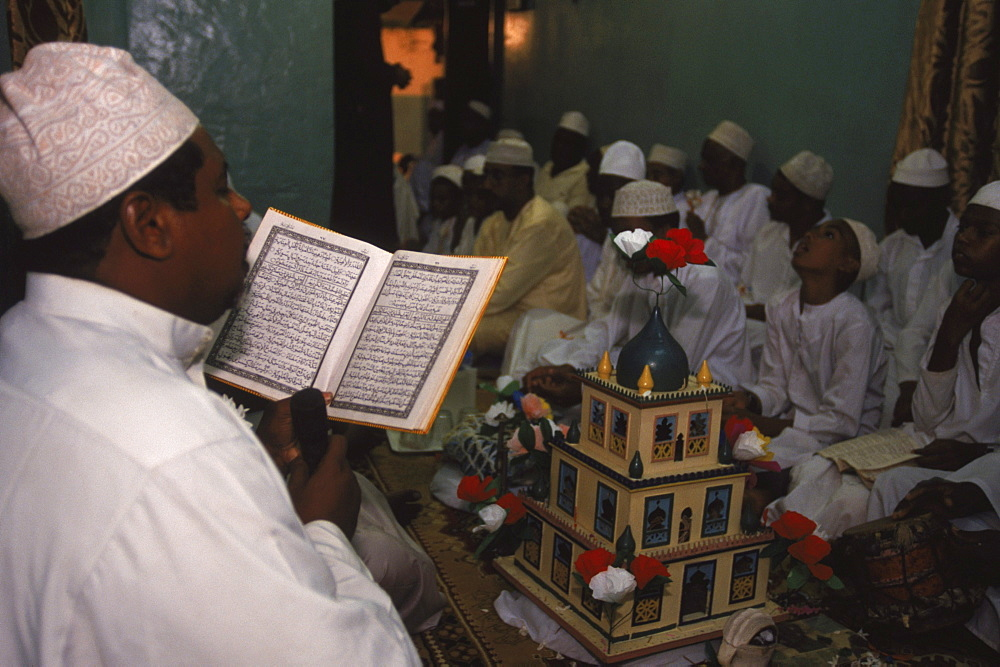A Swahili man reads from the Koran at a gathering of men in a house in Lamu to celebrate Maulidi, the birthday of the Prophet. Lamu Island, Kenya