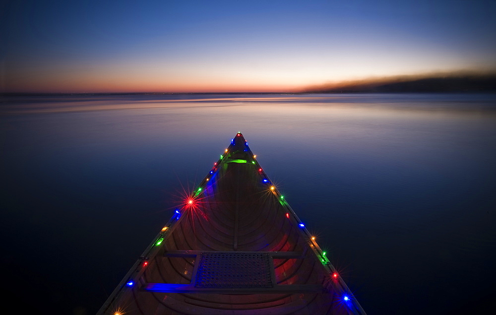 On a cold winter day a canoe decorated with Christmas lights floats on the last remaining open water on Lake Monona.