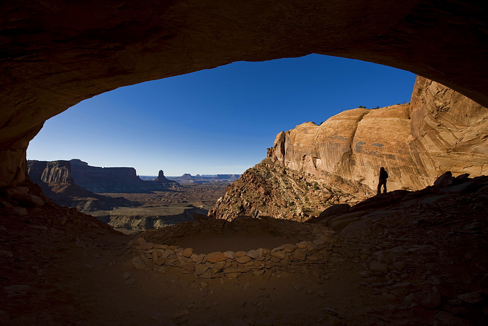 Person standing in alcove near indian ruin with view of desert, Canyonlands National Park, Utah.
