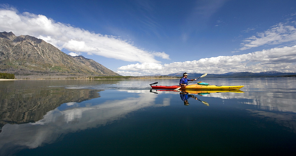 A kayaker rows across glassy waters of a lake with interesting reflections of mountains and clouds