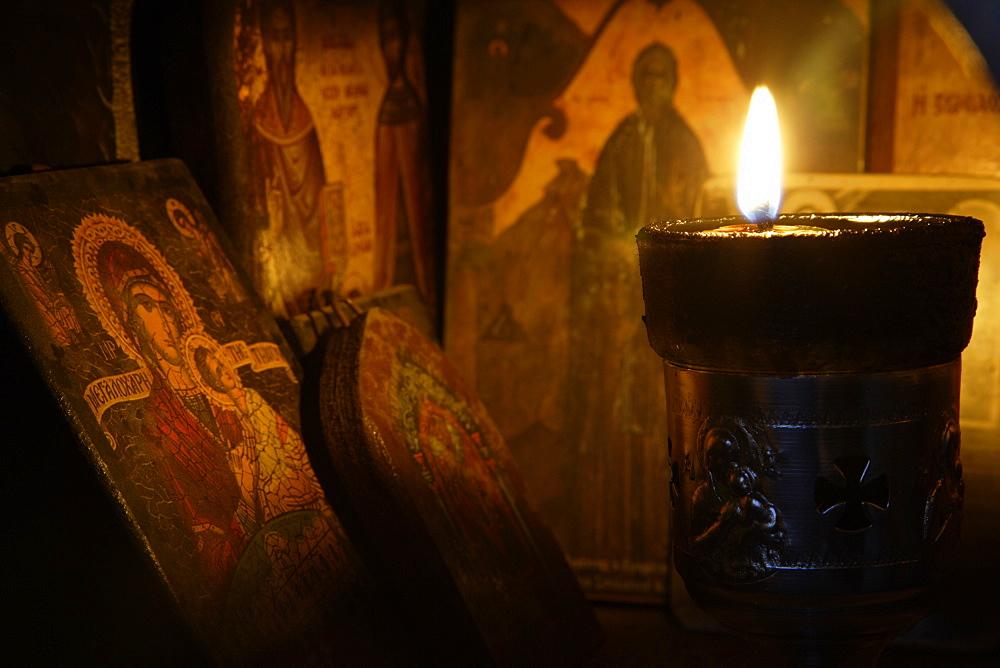 Icons and a lit candle inside a roadside, religious shrine. Crete. Greece