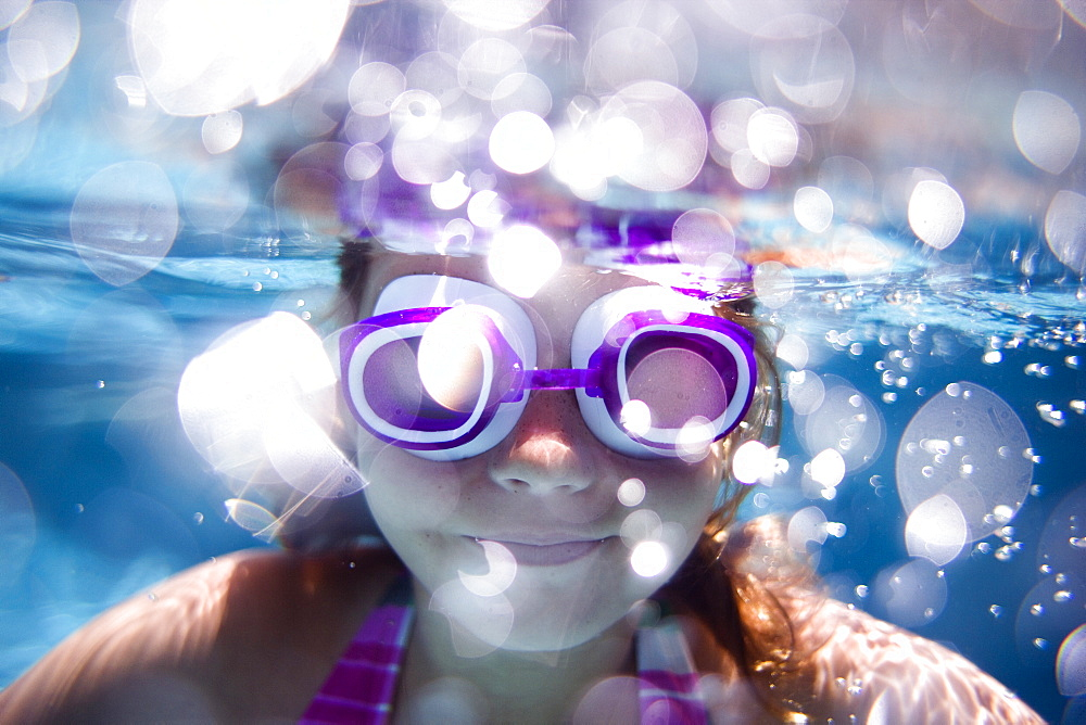 girl swimming in a pool looking at the camera wearing goggles