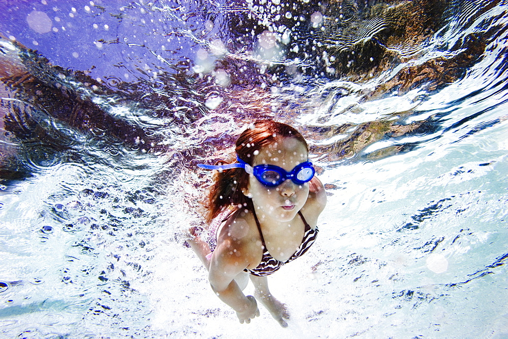 girl swimming towards the camera in a pool, wearing goggles
