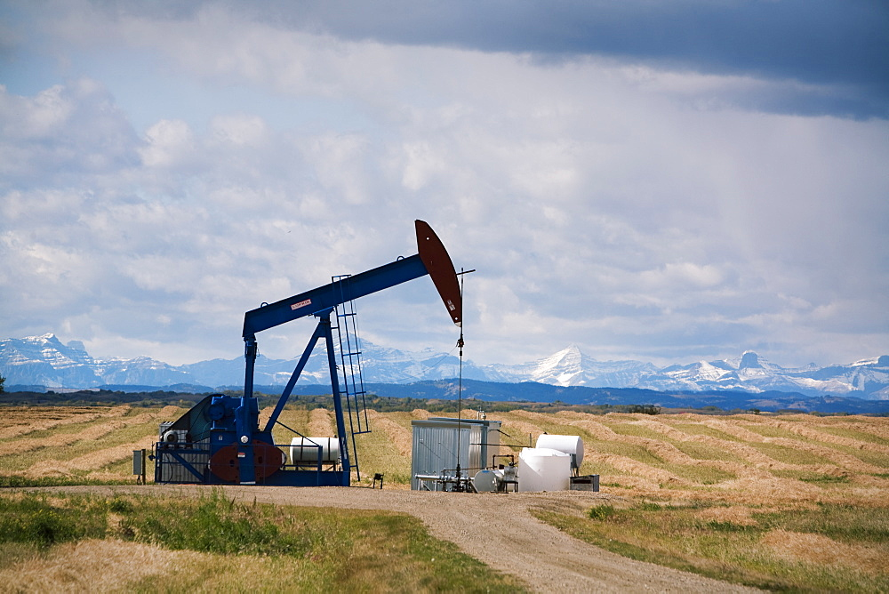 A pump jack pumps for oil in southern, Alberta, Canada with the Rocky Mountains for a backdrop.