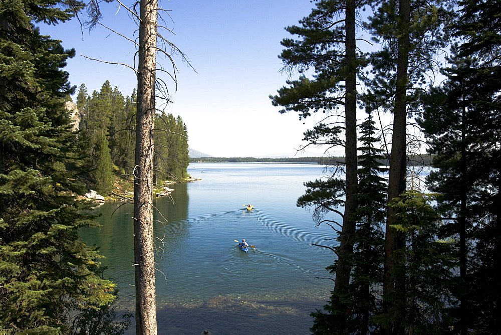 Kayakers leave the shore of Leigh Lake in Grand Teton National Park.
