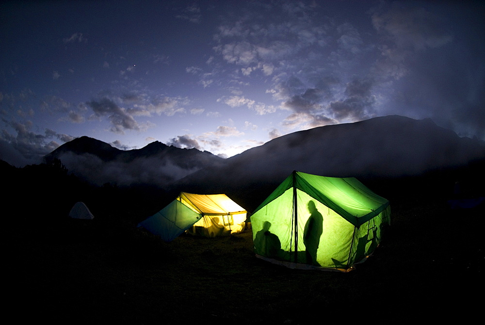 Resting at the foot of mountains, tents glow with light.