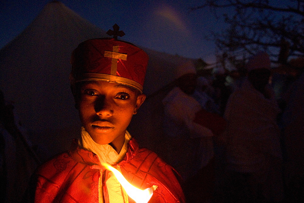 A boy dressed in ceremonial clothes  during night prayer during Timkat in Lalibela, Ethiopia.
