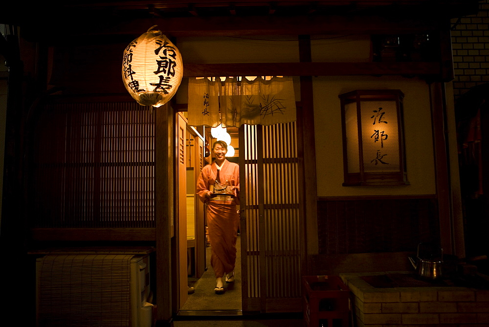 A woman going to serve her customers in a teahouse in Tokyo Japan.