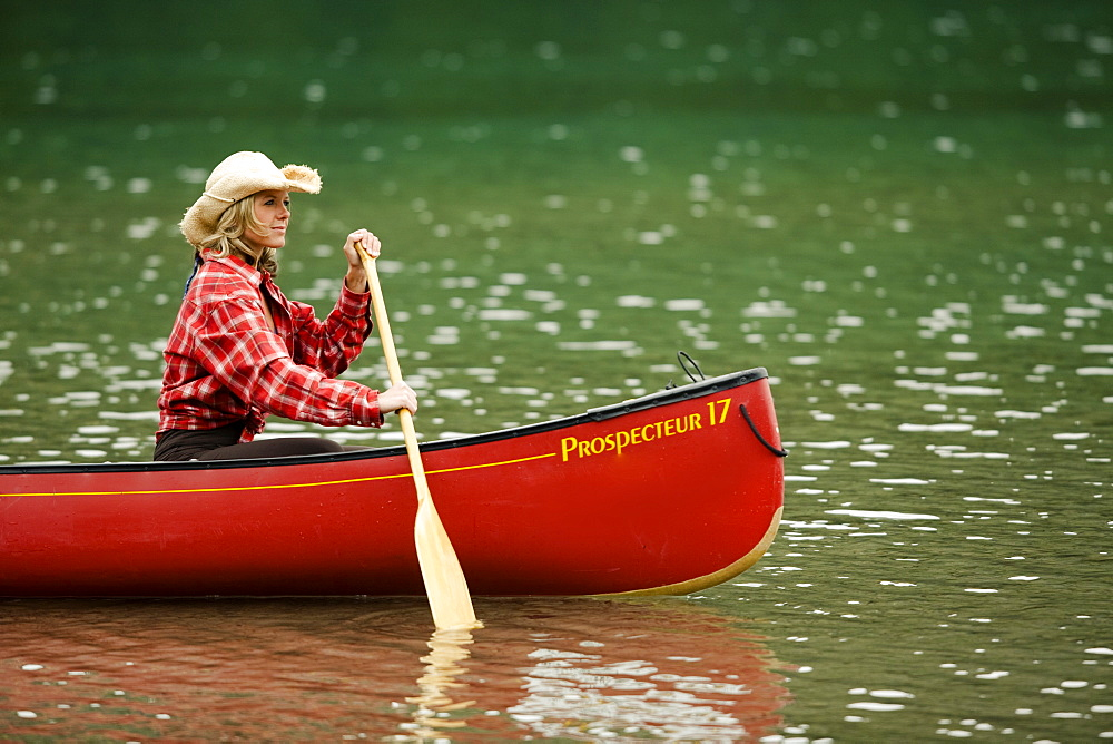 A woman canoes in a lake in Banff National Park, in Canada Alberta