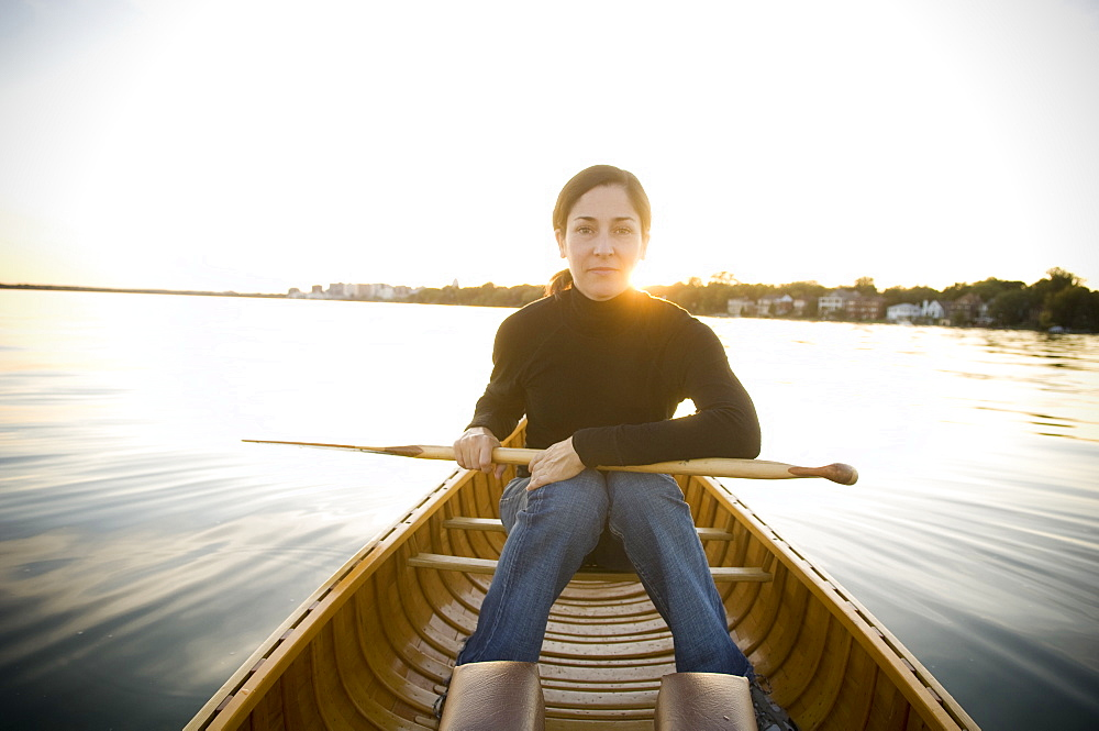 Mature Woman Holds Paddle On Lap In a Wood Canvas Canoe on a calm lake While Looking At Camera With Sun Setting In Background