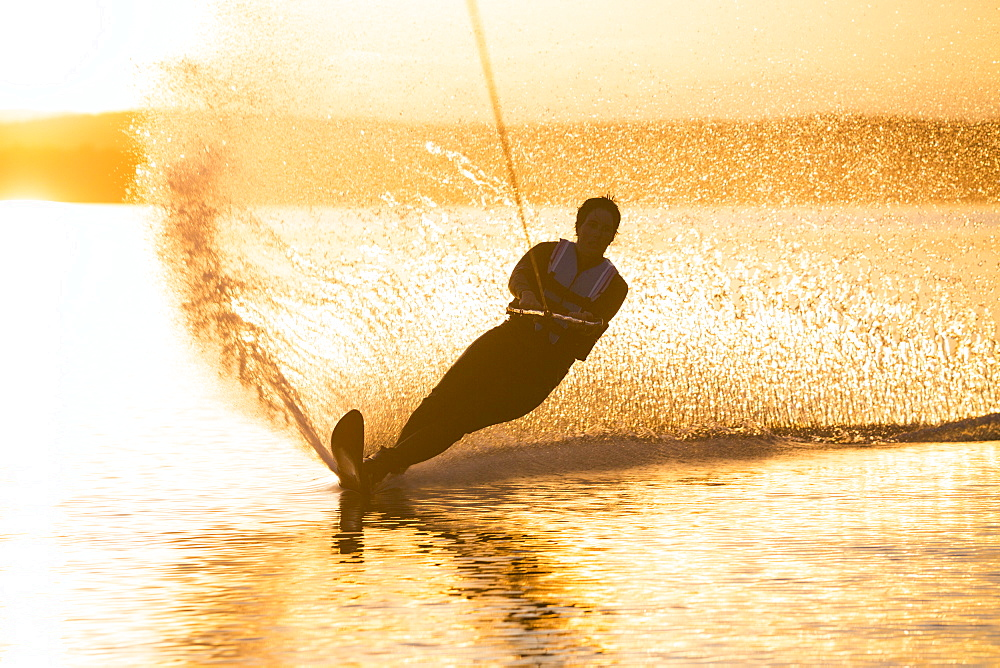 A woman water skis on Whitefish Lake at sunset in Whitefish, Montana.